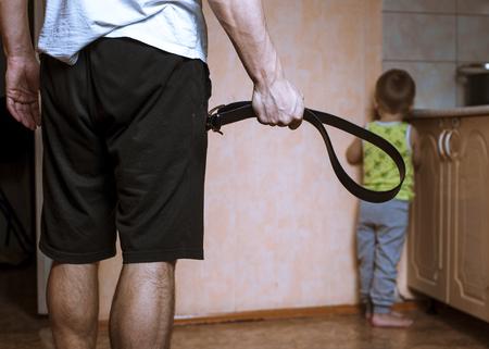parent agressif avec ceinture et enfant effrayé dans le coin. La violence domestique.