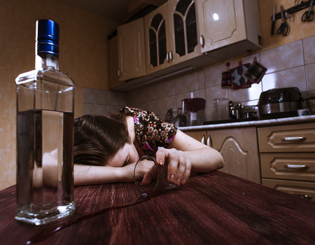 drunk girl: Sleeping drunk woman with inverted glass in hand. Alcoholic addiction.