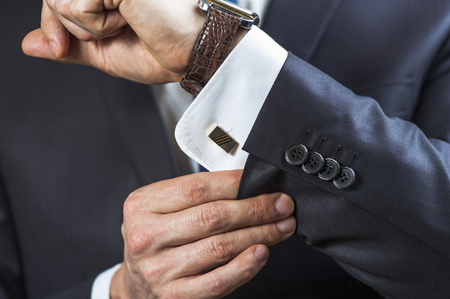 Elegant man correcting his cufflinks and sleeve. Imagens - 54511781