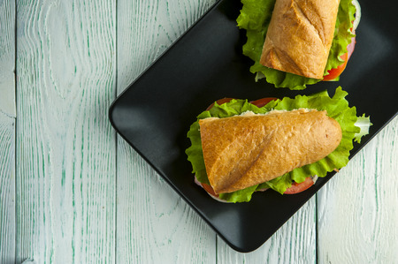 Delicious sandwiches with baguette, ham, vegetables and lettuce on black plate. Fast food.