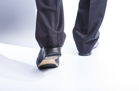 formal dressing: Mans legs in classic suit and leather shoes on white background. Stock Photo