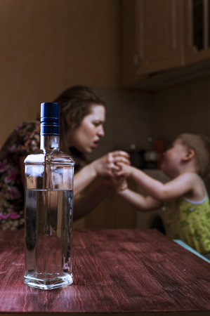 drunk girl: Drunk woman fights with her son. Family problems. Focus on bottle.