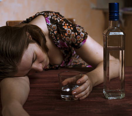 drunk girl: Young drunk woman holding her alcoholic drink and sleeping on the table