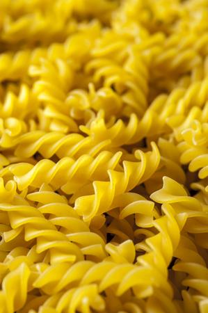 italian cuisine: Fusilli pasta background, close up. Italian cuisine. Vertical view.