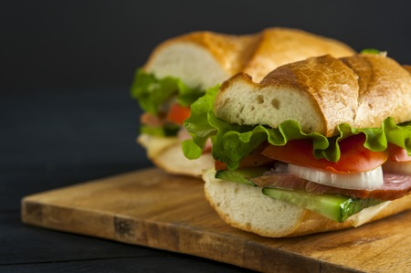Two delicious sandwiches with baguette, ham, tomato, onion, cucumber and lettuce on wooden table. Fast food Standard-Bild