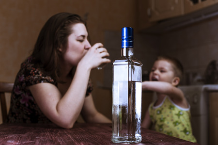 Drunk woman with glass and her crying son. Female alcoholism. Focus on bottle.