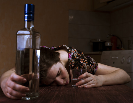 drunk girl: Tired drunk woman sleeping on the table and holding her glass. Focus on hand with glass. Stock Photo