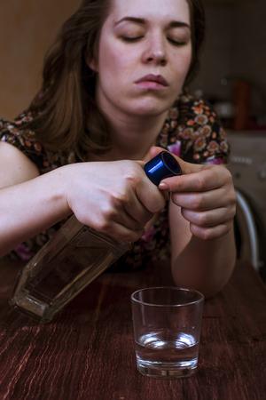 alcoholismo: Mujer bebida cansado tratando de abrir la botella con alcohol. alcoholismo en las mujeres. Foto de archivo