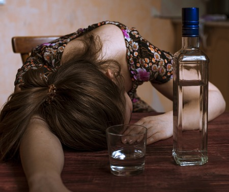 alcoholic drink: Drunk woman holding an alcoholic drink and sleeping with her head on the table