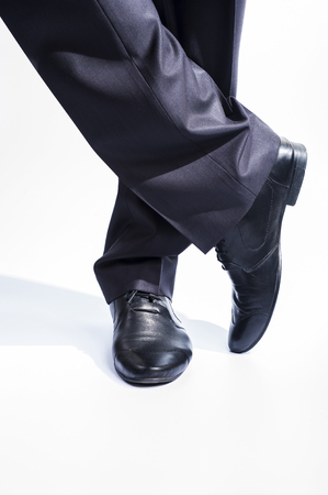 leather pants: Mans legs in classic suit and leather shoes on white background. Stock Photo