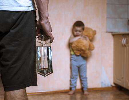 aggression: Drunk parent and little scared son with toy bear. Aggression in the family. Stock Photo