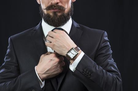 Elegant bearded man in suit correcting his tie. Preparation for work. Standard-Bild