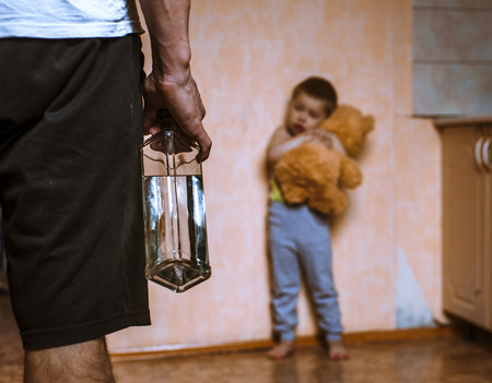 Drunk father and frifhtened child with toy bear. Domestic violence.