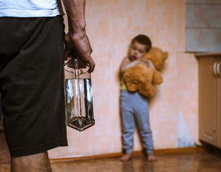 Dronken vader en frifhtened kind met stuk speelgoed draagt. Huiselijk geweld. Stockfoto