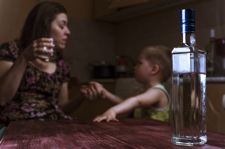 Drunk mother with alcoholic drink scolding her little son. Female alcoholism. Focus on bottle.