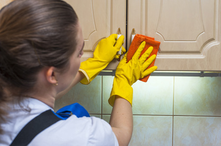 scrubbing: Female janitor scrubbing the kitchen cupboard with a rag. Housework and cleaning. Stock Photo