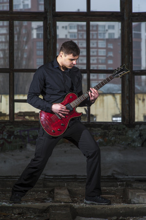 hand jamming: Portrait of Male musician playing on electric guitar on the background of cityscape.