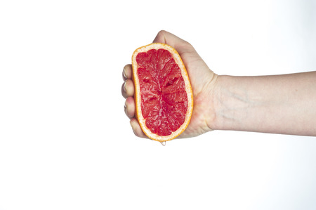 squeezing: Female hand squeezing grapefruit on white background.