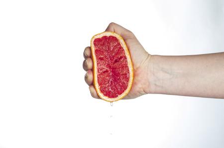 squeezing: Female hand squeezing grapefruit