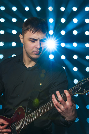 jamming: Man staying on stage and playing electric guitar