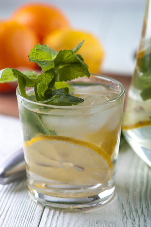 thin ice: Glass of detox drink water with mineral water, lemon slices and mint on wooden table.