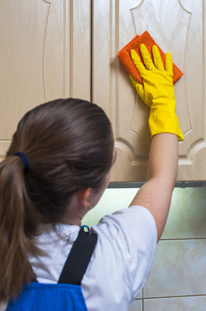 janitor: Female janitor in yellow gloves wiping kitchen cupboard with rag