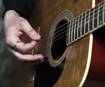 hand jamming: Acoustic guitar in mans hands, closeup. Stock Photo