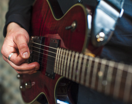 band bar: Closeup of mans hands playing on electric guitar