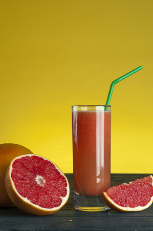 squeezed: Freshly squeezed grapefruit juice on wooden table. Stock Photo