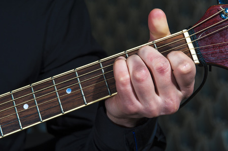 hand jamming: Mans hands playing on acoustic guitar, closeup.