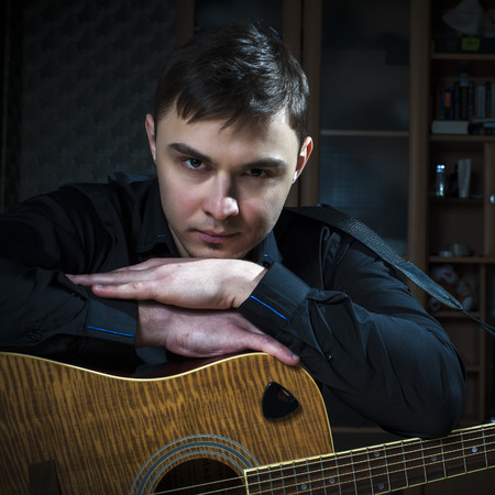 hand jamming: Portrait of wistful young man with guitar.