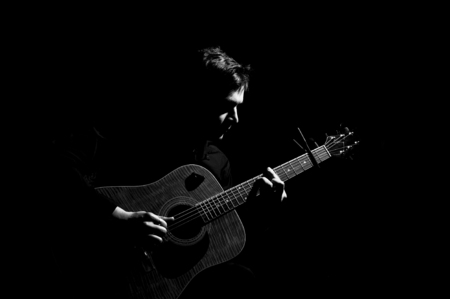 hand jamming: Male musician playing on acoustic guitar. Black and white photo.