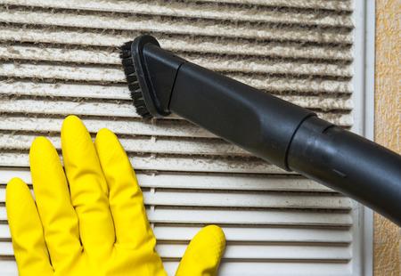 aire acondicionado: Mano en guante amarillo y el tubo aspirador. Ventilación de limpieza de la parrilla. Foto de archivo