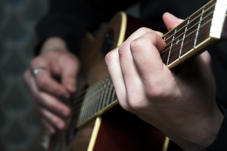 hand jamming: Closeup of acoustic guitar in mans hands.