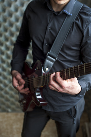 jamming: Young guitarist playing on electric guitar. Selective focus.