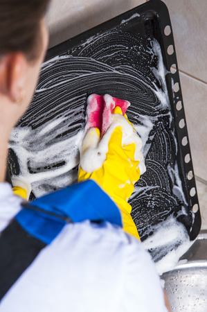 kitchen utensil: Woman washing greasy pan with sponge. Housework and cleaning concept. Stock Photo