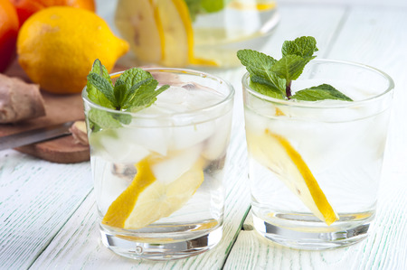 thin ice: Two glasses of detox drink with lemon slices, mint leaves and mineral water on wooden table.