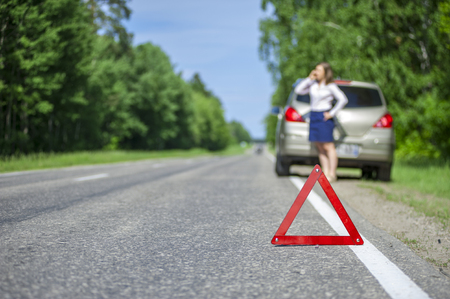 road assistance: Young woman calling for car assistance after breakdown on the road. Focus on red triangle warning sign.
