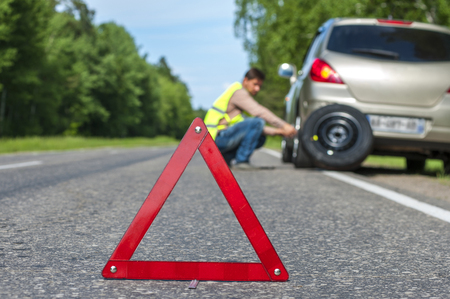 Male driver in reflective vest changing tire after breakdown. Focus on red warning triangle sign.