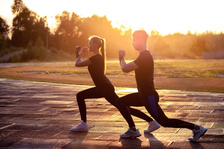 Two silhouettes of fit young man and woman doing lunges outdoors at sunset. Fitness or running workout outdoors Фото со стока