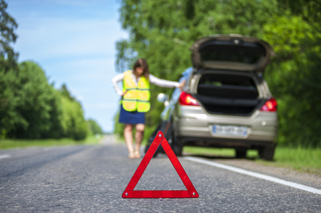 emergency vest: Woman in reflective vest near broken car on the roadside. Focus on red triangle warning sign Stock Photo