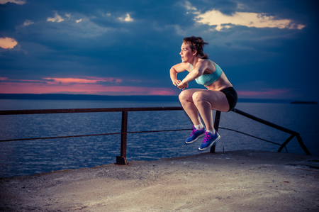 Young strong woman in sportswear doing plyometric exercises on pier. Jump squats, fitness workout outdoors. Фото со стока