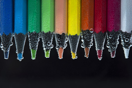 peachy: Bright colorful pencils in water with bubbles. Back to school concept Stock Photo