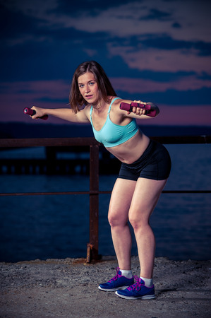Young healthy woman doing exercises with dumbbells. Fitness workout outdoors. Stock Photo