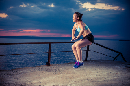 Young woman in sportswear on sea pier doing squat jumps. Fitness workout outdoors.