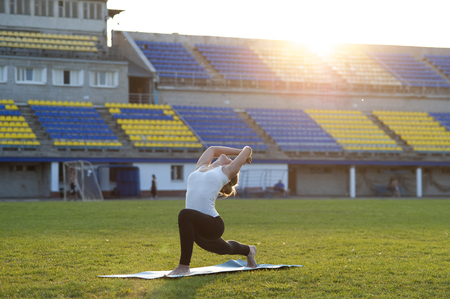 lunge: Young flexible woman practicing yoga in park. High Lunge Pose.
