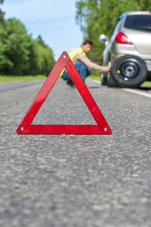 emergency vest: Man in reflective vest changing the tire after car breakdown. Focus on red triangle emergency sign. Stock Photo