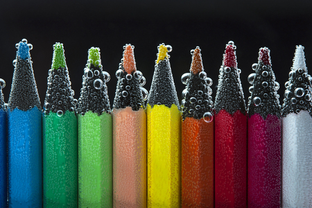 peachy: Colorful pencils in sparkling water. Back to school concept. Stock Photo