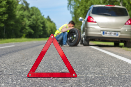warning vest: Male driver in reflective vest with spare wheel on the roadside, broken car and red triangle warning sign. Focus on red sign Stock Photo