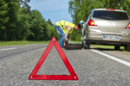 Man in reflective vest changing tire after breakdown. focus on red triangle warning sign.